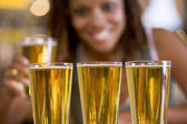 Three beers in a row, with young woman in background — Stock Photo