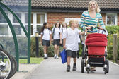 A woman with a pushchair walking her son home from school — Stockfoto