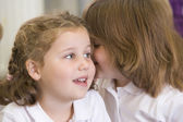 A schoolgirl whispers to her friend in a primary class — Stock Photo