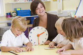Teacher helping schoolchildren learn to tell time in primary cla — Stock Photo