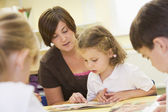 Schoolchildren and their teacher reading in a primary class — Stock Photo