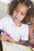 Girl learning to write numbers in primary class — Stock Photo