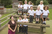 Young children and their teacher posing for a class photo — Stock Photo
