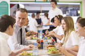 A teacher eating lunch with his students in the school cafeteria — Stock Photo