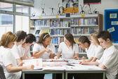 Schoolchildren studying in school library — Stock Photo