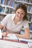 Dziewczyna student studia w bibliotece — Zdjęcie stockowe