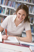 Girl student studying in library — Stockfoto