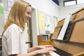 Schoolgirl playing piano in music class — Stock Photo