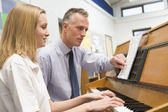 Teacher with schoolgirl playing piano in music class — Stock Photo
