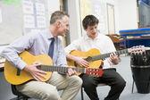 Scolaro e maestro suonando la chitarra in classe di musica — Foto Stock
