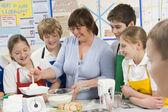 Crianças em idade escolar e professora da escola em uma aula de culinária — Foto Stock