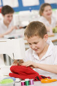 Schoolboy using a sewing machine in sewing class — Stock Photo