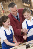 Schoolgirls and teacher in woodwork class — Stock Photo