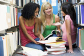 Three students working together in library — Stok fotoğraf