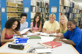 Group of university students working in library — Foto Stock