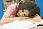 Exhausted university student in library — Stock Photo