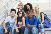 Group of university students sitting on steps — Stock Photo