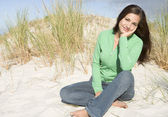 Young woman relaxing amongst dunes — Stock Photo