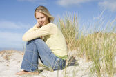 Young woman sitting amongst dunes — Stock Photo