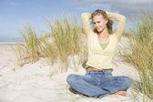 Young woman relaxing amongst dunes — Stock Photo