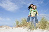 Two young women having fun in dunes — Stock Photo