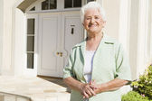 Senior woman standing outside house — Stockfoto