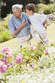 Grandfather and grandson outdoors in garden talking and smiling — Stock Photo
