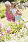 Grandmother and granddaughter outdoors in garden smiling — Stock Photo