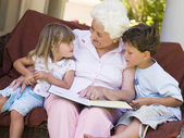 Grandmother reading to grandchildren — Stock Photo