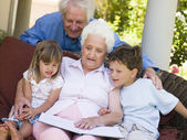 Grandparents reading to grandchildren — Stock Photo