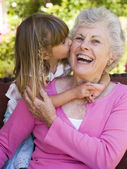 Grandmother getting a kiss from granddaughter — Foto Stock