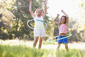 Grandmother and granddaughter at a park hula hooping and smiling — Stock Photo