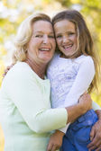 Grandmother and granddaughter outdoors and smiling — Stock Photo