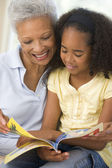 Grandmother and granddaughter reading and smiling — Stock Photo