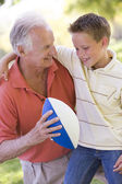 Grandfather and grandson outdoors with football smiling — Stock Photo