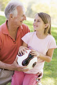 Grandfather and granddaughter outdoors with ball smiling — Stock Photo