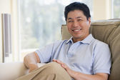 Man sitting in living room smiling — Stock Photo