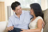 Couple relaxing in living room talking and smiling — Stock Photo