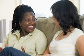 Two women talking in living room and smiling — Stock Photo