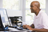 Man in home office using computer and smiling — Stock Photo