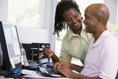 Couple in home office with credit card using computer and smilin — Stockfoto