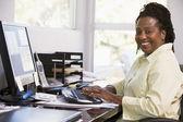 Mujer en oficina en casa usando computadoras y sonriendo — Foto de Stock