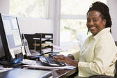 Woman in home office using computer and smiling — ストック写真