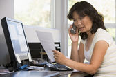 Woman in home office with paperwork using telephone — Stock Photo