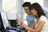 Couple in home office with computer and paperwork smiling — Stock Photo