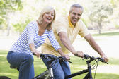 Couple on bikes outdoors smiling — Foto de Stock