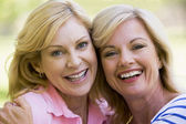 Two women outdoors embracing and smiling — Stock Photo
