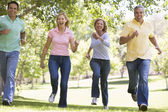 Two couples running outdoors smiling — Stock Photo