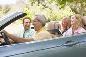 Two couples in convertible car smiling — Stock Photo