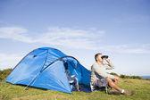 Man camping outdoors and looking through binoculars — Stock Photo